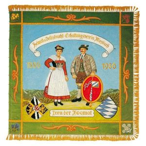 Precious old homeland club flag with couple in typical Miesbach costume in front of mountain silhouette